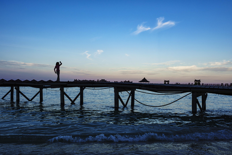Girl dancing on Sipaidan Water Village pier at dusk